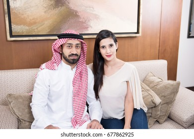 Arab couple at home sitting in traditional dress
