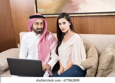 Arab couple at home in traditional dress using laptop
