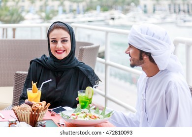 Arab couple looking at each other after dining in Dubai UAE.