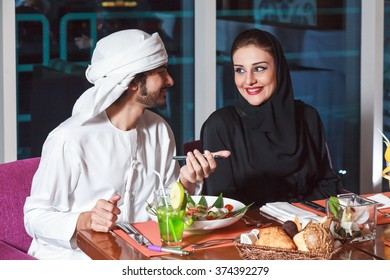 Arab couple looking talking and discussing while dining in a restaurant in Dubai UAE.
