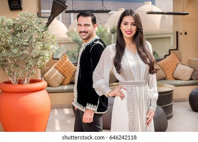 Arab couple standing and looking in the camera. Couple dressedin traditional Middle Eastern closes. Ramadan Holiday theme.