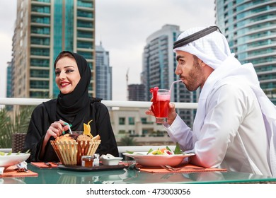Arab couple talking to each other while the man is drinking a juice after dining in Dubai UAE.