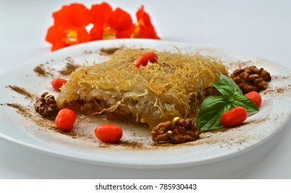 Arab dessert with sugar syrup and walnuts.  Kadaif in a plate on a white background.