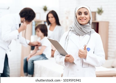 An Arab doctor in hijab poses with a history of the disease in his hands. Arabian hospital concept. Pediatrician office and sick child.