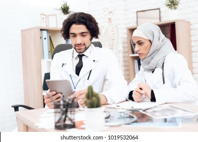 An Arab doctor is showing something on a tablet to a colleague. An Arab woman wears a hijab. Arabian hospital concept.