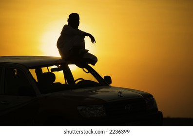 Arab driver sitting on the top of his overland car