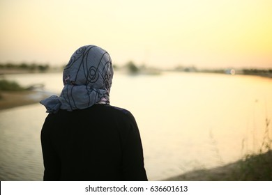 Arab, Emirate indian, asian or middle eastern Woman. Girl standing in lake side. Muslim lady standing near beautiful landscape. Back side of traditional dress and scarf, young adult human female.