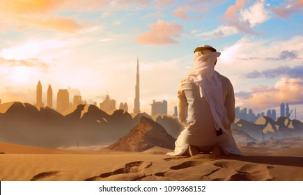 Arab Emirati man praying on top of a dune in UAE desert front Dubai skyline.