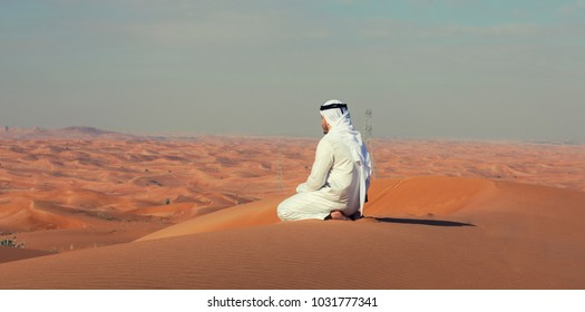 Arab Emirati man sitting on top of a dune in UAE desert