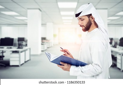 Arab Emirati man writing on a book, working in office
