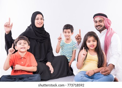 Arab family sitting at home with white background