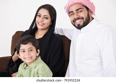 Arab family sitting on sofa chair at home enjoying the time with white background