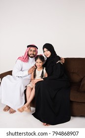 Arab family sitting on sofa chair at home with white background