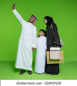 Arab family taking selfie using mobile camera