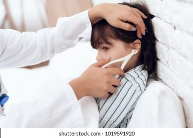 An Arab female doctor examines a sick boy. He has a cold. He lies in bed. The doctor will treat him.