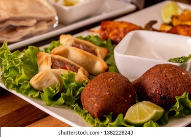 Arab Food, Kibe and sfiha with white sauce about a wood table