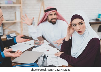 Arab girl turned away from her husband who yells at her. Couple sitting in the office of a realtor and quarreling over the purchase of a new home.