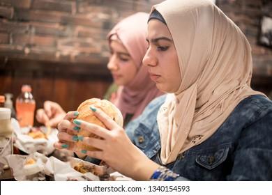 Arab girls at fast food restaurant eating burger