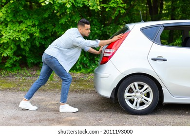 Arab guy in stylish casual outfit pushing broken car, side view. Middle-eastern man travelling with friends or lover, got stuck on the road to countryside, pushing automobile hatchback