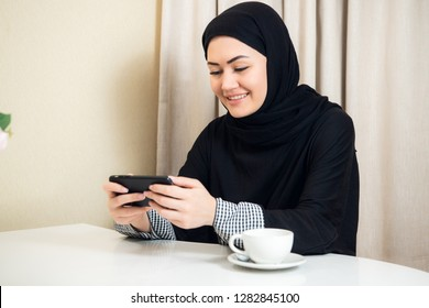 Arab happy casual woman using a smart phone at home