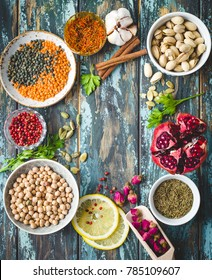 Arab ingredients for middle eastern food. Arabic cuisine ingredients. Background. Chickpea, lentils, rose buds, lemon, spices, pomegranate, pistachios. Halal food making. Space for text. Top view