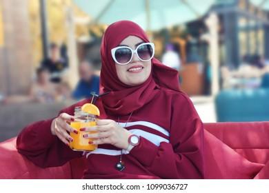 Arab lady wearing red modern baya and hijab sitting in coffeeshop and drink orange juce