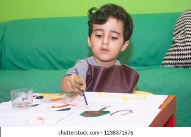 Arab little boy painting sketchpad with a brush and water color paint, close up of his hands, child hoppy
