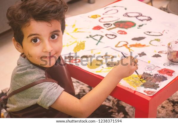 Arabischer kleiner Junge, der Skizzenpaddel mit einer Farbe aus Pinsel und Wasser, Nahaufnahme seiner Hände, Kindermohn