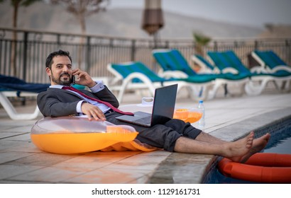 Arab man by the pool working in his laptop