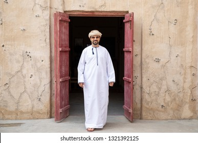 arab man coming out of an old building in old Al Seef part of Dubai, United Arab Emirates