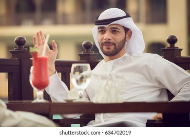 Arab man is drinking coffee in a cafe. He sits at a table in a cafe, and drink red juice at Dubai in evening