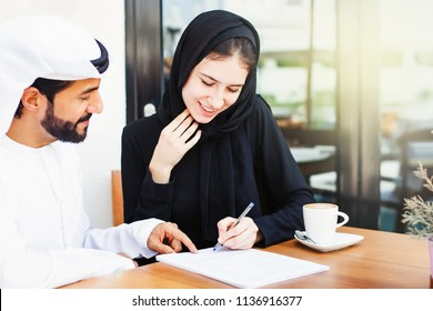 Arab man giving documents to sign to a woman in hijab