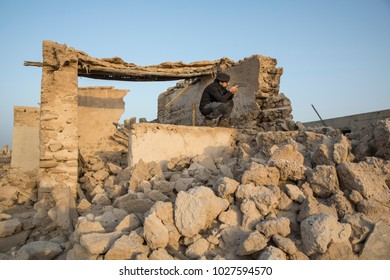 arab man with a gun in a middle of destroyed village