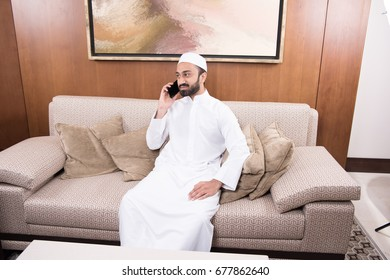 Arab man at home in traditional dress using his mobile phone