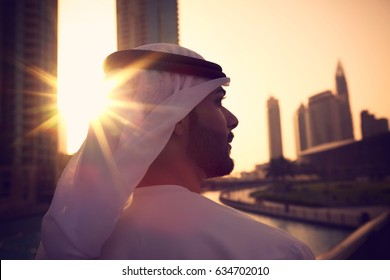 Arab man with kandura enjoying sunrise in Dubai proud of his country,