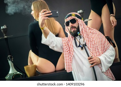 An Arab man in a keffiyeh with a hookah takes a selfie against the background of beautiful girls. Hookah party. Clubbing entertainment. Hookah exhibition. Russia. Saint-Petersburg. 10.03.2019