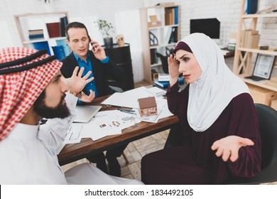 Arab man in kufiya is arguing with Arab woman in hijab in office of realtor. Muslim couple is quarreling in office of real estate agency.
