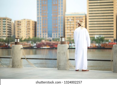 arab man in old Al Seef part of Dubai, United Arab Emirates, looking at the buiuldings by the greek side