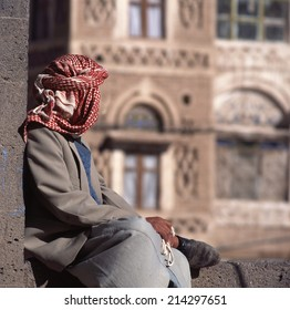 Arab man, seen from the back, with veil. At background typical Yemen house in Sanaa the capital of yemen.