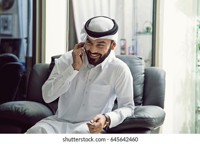 Arab man is smiling and talking on phone