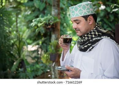 Arab man standing and drinking black coffee.