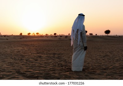 Arab man stands alone in the desert and watching the sunset