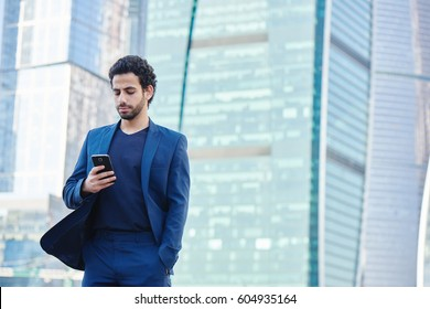 Arab man in suit holding a phone and looking at him with skyscrapers in the background