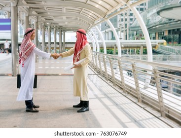 Arab man teamwork shaking hands after successful meeting outdoor. Successful businessmen handshaking after negotiation on city background. Partnership concept. Background and copy space.