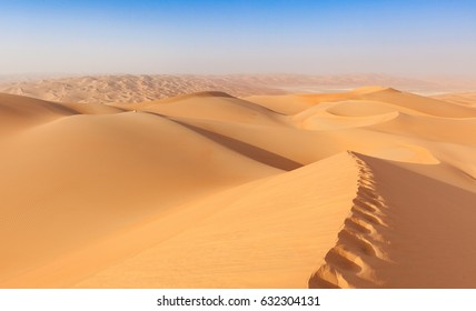 arab man in tradition outfit sitting over a Dune in arabian Dese