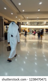 Arab man in traditional clothes went for shopping in the city mall