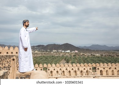 arab man in traditional omani outfit pointing to the distance