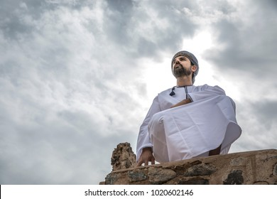 arab man in traditional omani outfit resting with a cloudy sky at the background