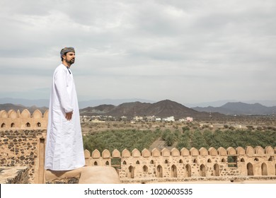 arab man in traditional omani outfit overlooking the countryside of oman