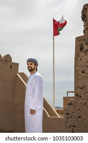 arab man in traditional omani outfit with omani flag flying at the background